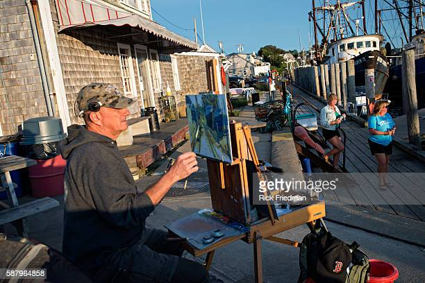 Artist Kevin Shea painting Menemsha Harbor in the Town of Chilmark on Martha's Vineyard MA on August 15 2013 Menemsha is a fishing village best known...