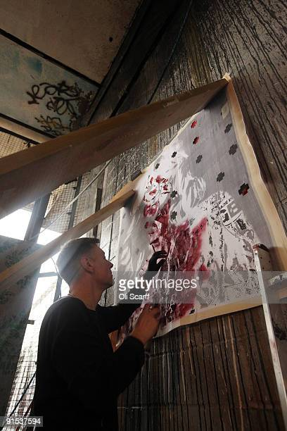 Artist 'KGuy' puts the finishing touches to his artwork in the 'One Foot in the Grove' exhibition of street art by 'Mutate Britain' under the Westway...