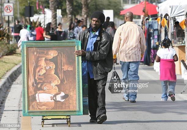 Artist Kolongi Bratiwaite rolls a painting down Kennedy Boulevard January 24 in Eatonville Florida The city of Eatonville hosted the annual Zora...