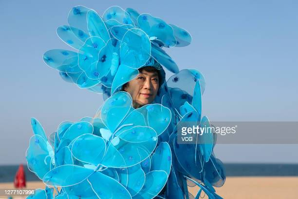 Artist Kong Ning wearing her 'blue butterfly' art installation conducts a performance art to raise awareness of marine environment protection on...