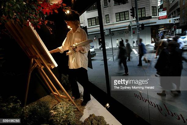 Artist Leahlani Johnson centre paints a floral still life in the David Jones window display on Market Street Sydney as pedestrians stop to admire her...