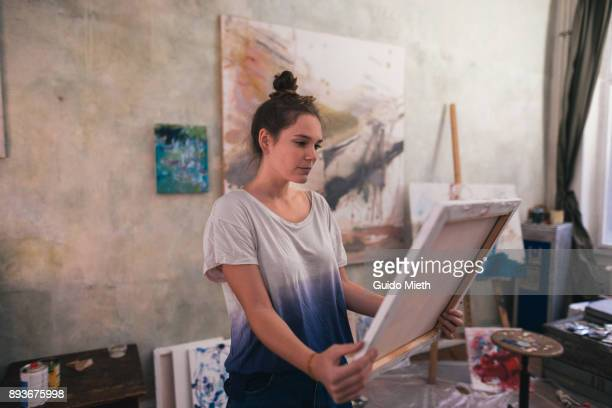 Artist looking at fresh painting in atelier.