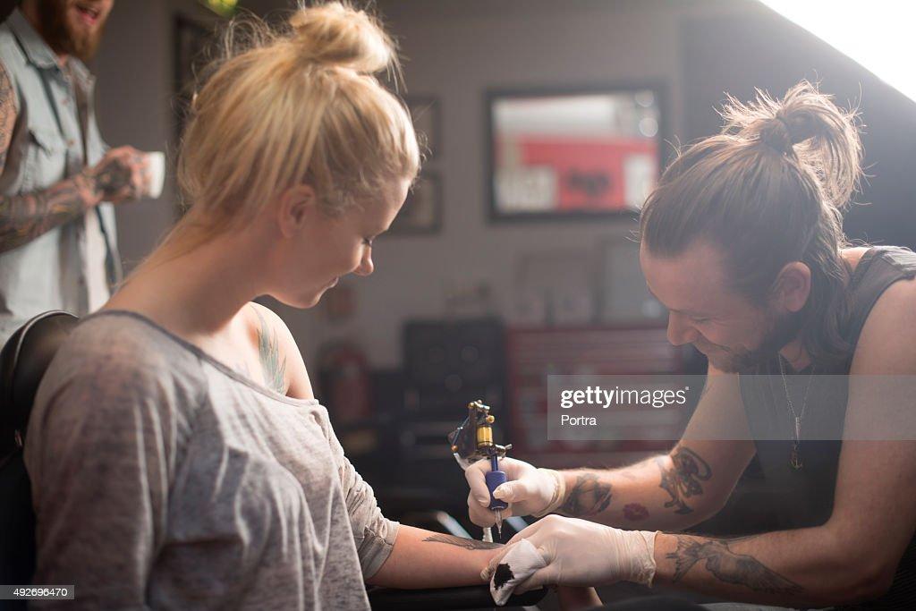 Künstler, tattoo auf weibliche Kunden hand : Stock-Foto