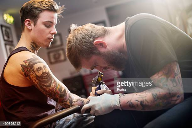 Artist making tattoo on man's hand