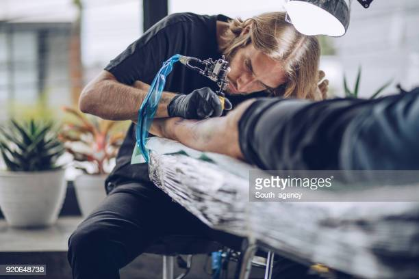 artist making tattoo on man's leg in studio - south_agency stock pictures, royalty-free photos & images