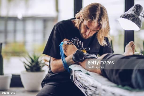 Artiste en tatouage sur la jambe de l'homme