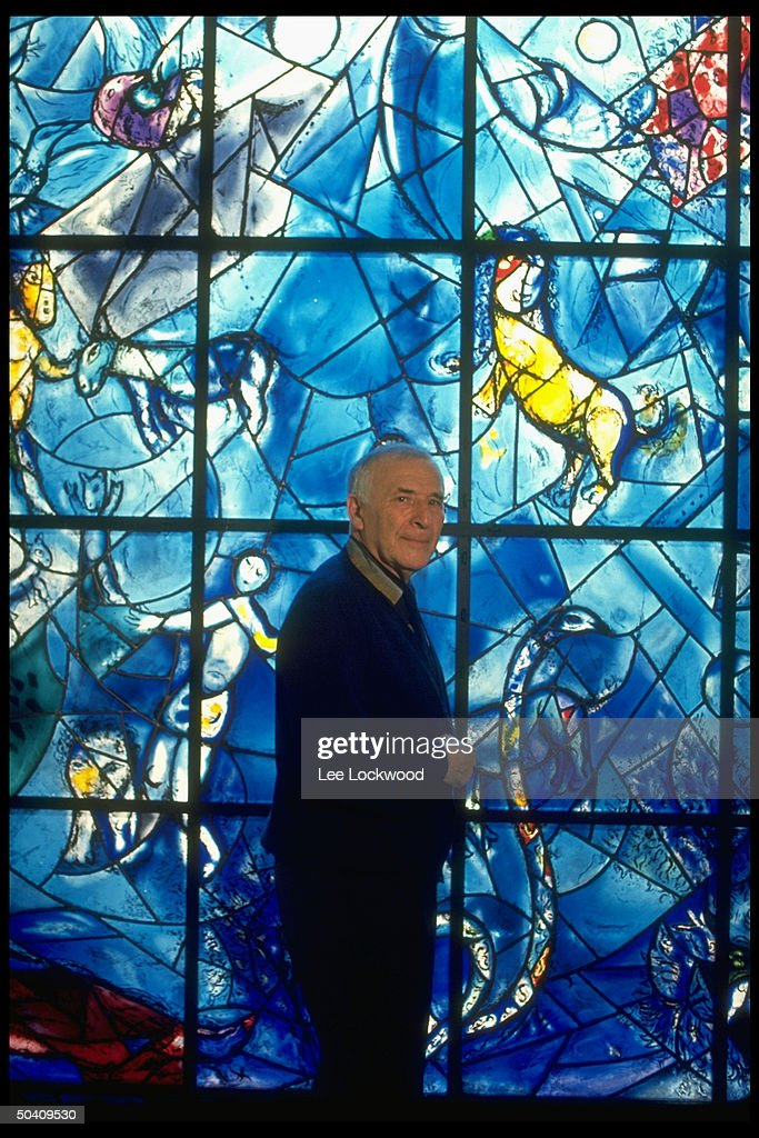 Artist Marc Chagall standing in front of his stained glass window installed at the United Nations.