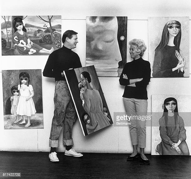 """Artist Margaret Keane standing next to her painting: """"Time in the Mind"""" ; her husband, Walter Keane holds his painting """"We Will Overcome."""""""