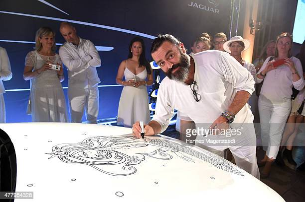 Artist Mauro Bergonzoli paints on the new Jaguar XE during the Jaguar White Night at Wandelhalle Bad Wiessee on June 20 2015 in Bad Wiessee Germany
