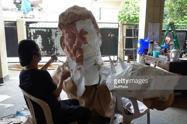 Artist Max Santiago paints a part of an effigy of President Rodrigo Duterte which will be used in the protest coinciding President Rodrigo Duterte's...