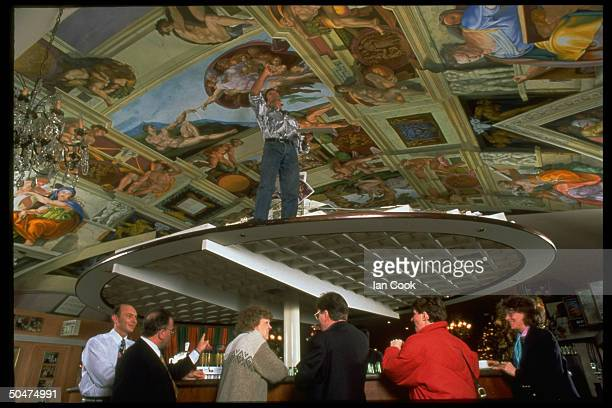 Artist Michael Browne adding finishing touches to his reproduction of Michelangelo's Sistine Chapel on ceiling of Italian restaurant Cocotoo