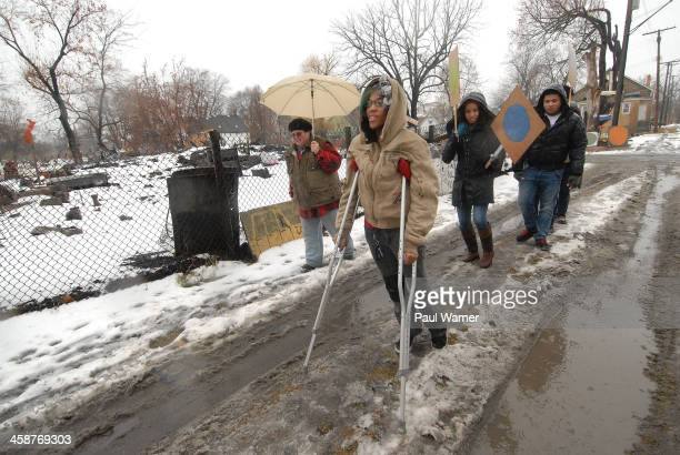 Artist Mina Way walks with crutches during the March For Artistic Freedom and Winter Solstice Event at Heidelberg Project on December 21 2013 in...
