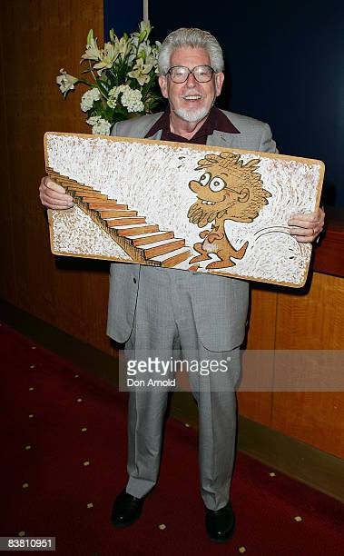Artist musician and author Rolf Harris poses with his wobble board during a literary lunch to promote his latest book 'Tie Me Kangaroo Down Sport' at...