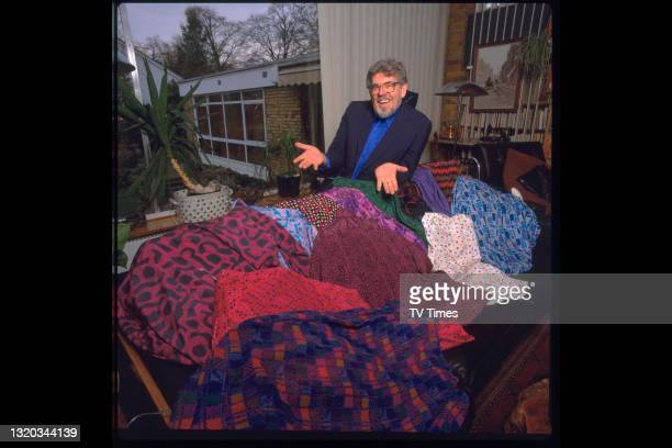 Artist, musician and television presenter Rolf Harris photographed at home with a selection of his colourful shirts, circa 1991.