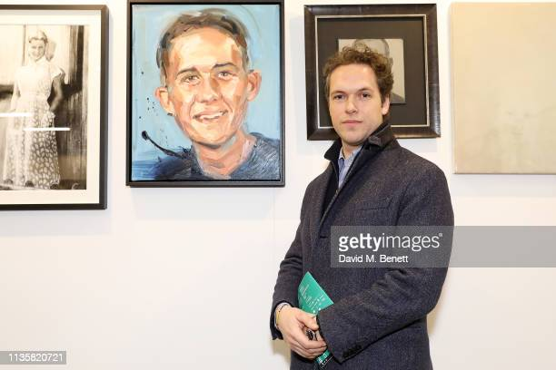 Artist Nicholas Todhunter poses with his portrait from the Unmissable25 exhibition during the private view of The Other Art Fair at The Old Truman...