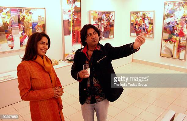 Artist Niladri Paul describing about his paintings to a lady during his painting exhibition named 'Concert of Colours' at Santushti Shopping Arcade...