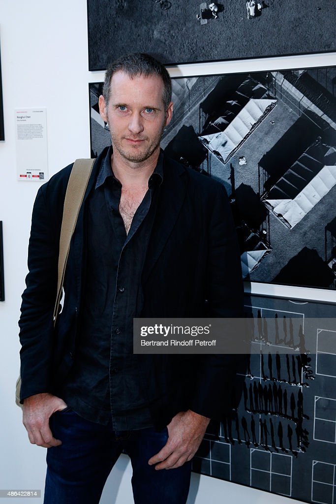 Artist of the Exhibition Tomas Van Houtryve poses in front of his works during the 'World Press Photo 2015' Exhibition Opening Party, held at Galerie Azzedine Alaïa on September 3, 2015 in Paris, France.