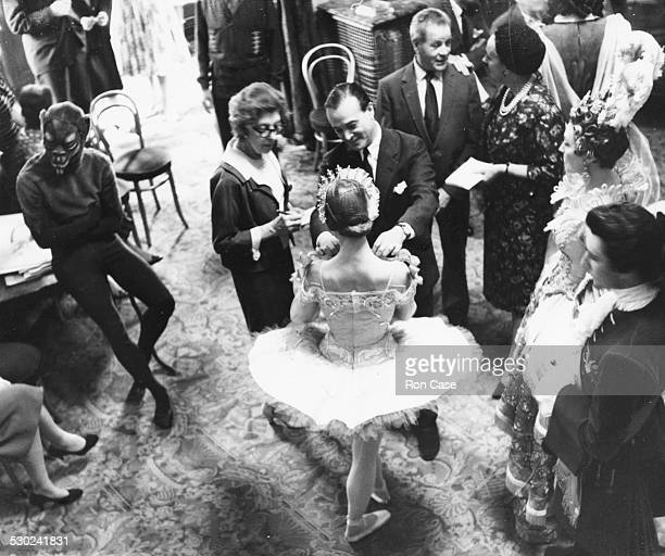 Artist Oliver Messel inspecting the costume he designed worn by ballerina Nadia Nerina watched by other cast members behind the scenes of the ballet...