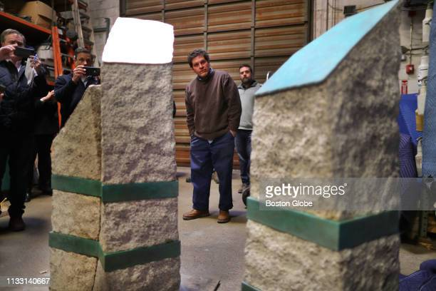 Artist Pablo Eduardo who is overseeing the memorials to the victims of the 2013 Boston Marathon bombings stands between the three granite monuments...
