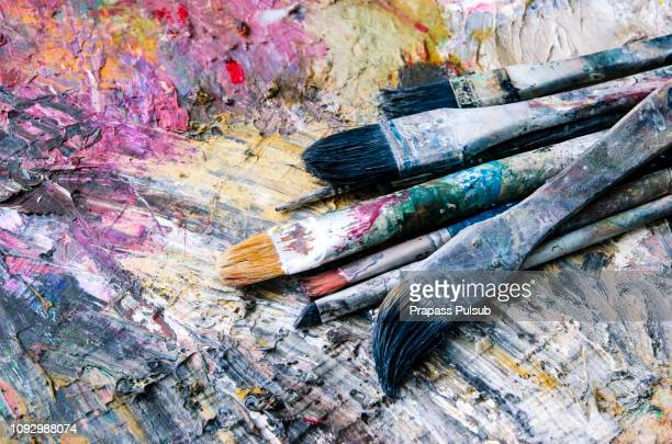 artist paint brushes and palette on wooden background - artist's palette stock pictures, royalty-free photos & images