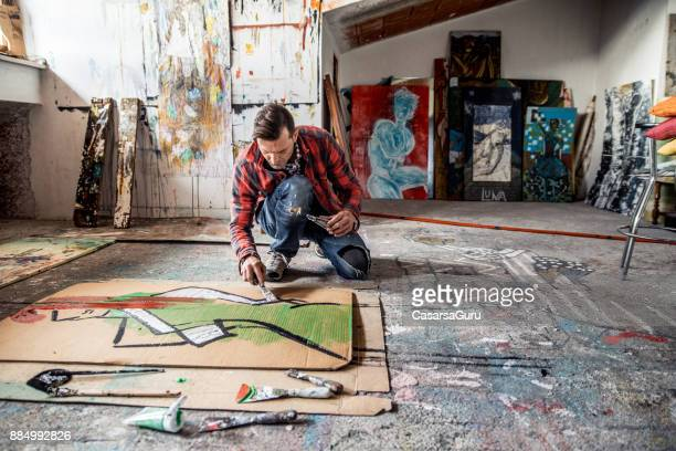 artist painting canvas cardboard on floor - artistic product stock pictures, royalty-free photos & images