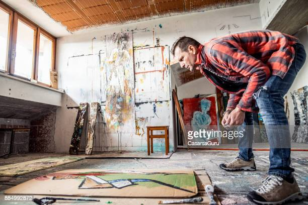 artist painting canvas cardboard on floor - bending over stock pictures, royalty-free photos & images