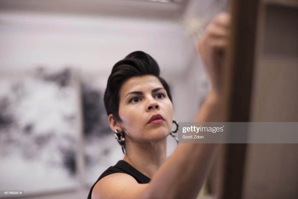 Artist painting in her studio : Stock Photo