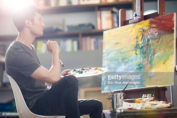 artist painting in his studio - 美術スタジオ ストックフォトと画像