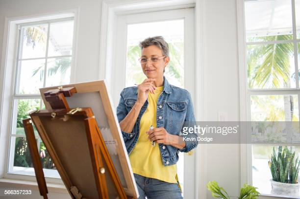Artist painting on easel in sun room