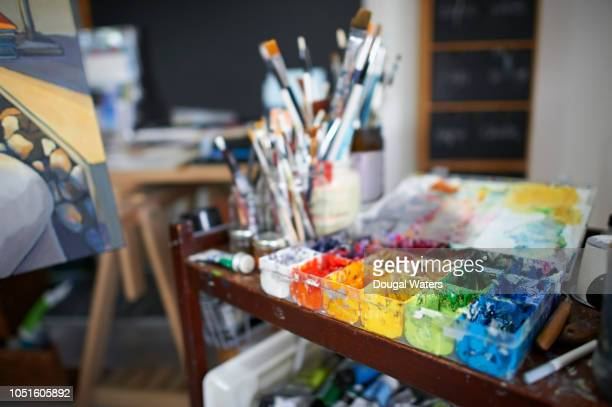Artist paints and canvas painting in studio.