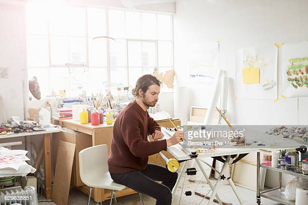 Artist paints in art studio.