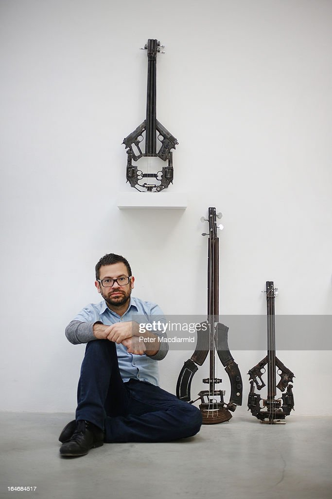 Artist Pedro Reyes sits with some of his musical instruments sculpted from recycled guns at the Lisson Gallery on March 26, 2013 in London, England. Mexican artist Pedro Reyes received 6,700 destroyed weapons from the Mexican government from which he sculpted two groups of instruments. The first, a series titled Imagine, is an orchestra of fifty instruments, from flutes to string and percussion instruments, designed to be played live. The second, Disarm, is an installation of mechanical musical instruments, which can either be automated or played live by an individual operator using a laptop computer or midi keyboard.