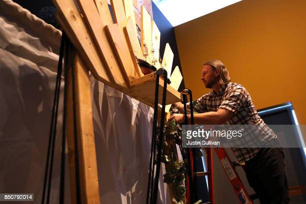 """Artist Peter Foucaulton works on his """"Ghost Ship"""" art installation at the Oakland Museum of California on September 21, 2017 in Oakland, California...."""