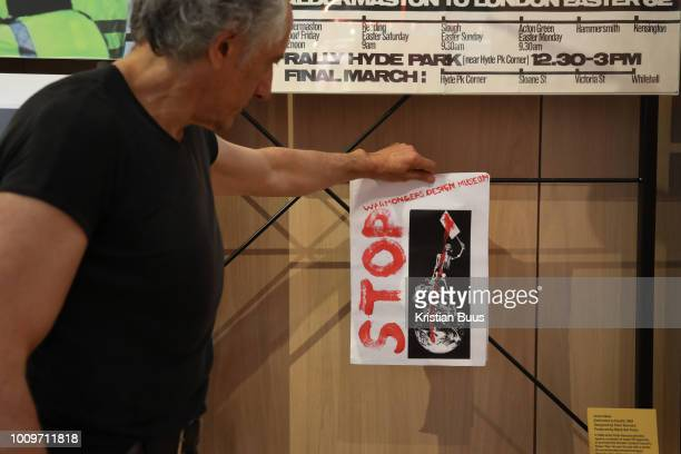 Artist Peter Kennard holds up a small poster in protest instead of his art work on show up till yesterday at the Design Museum, London, Unted...