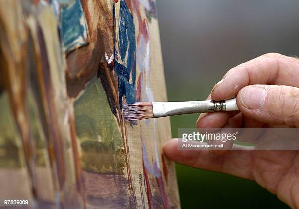 Artist Peter Williams applies a delicate bursh to a panoramic painting of the paddock before the 130th running of the Kentucky Derby May 1 2004 at...