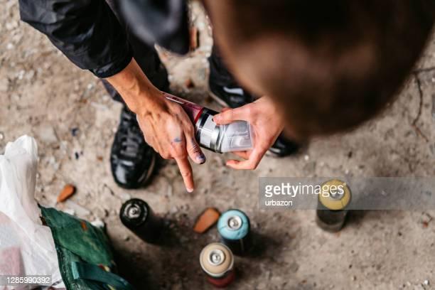 artist picking aerosol paint spray bottle - vandalism stock pictures, royalty-free photos & images