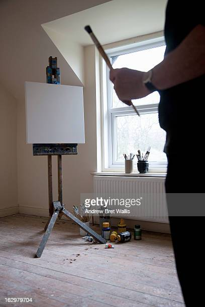 Artist poised with brush in hand near blank canvas