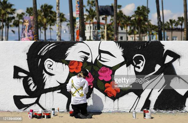Artist Pony Wave paints a scene depicting two people kissing while wearing face masks on Venice Beach on March 21 2020 in Venice California...