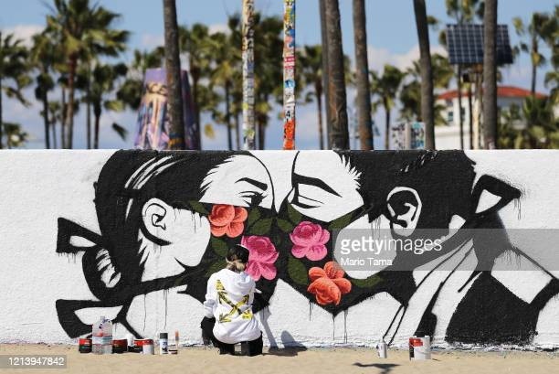 Artist Pony Wave paints a scene depicting two people kissing while wearing face masks on Venice Beach on March 21, 2020 in Venice, California....