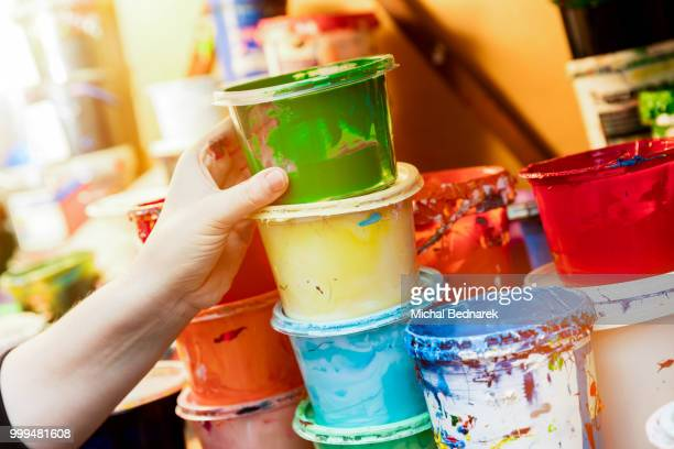 Artist reaching for a liquid paint container.