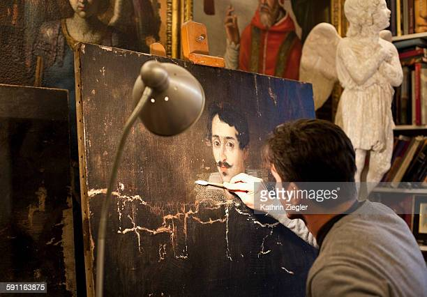 artist restoring a painting in his studio