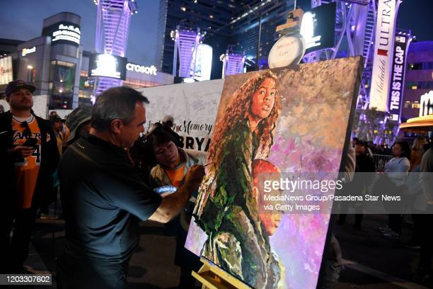 Artist Reza Safa of Cornoa Del Mar works on a painting of Kobe and Gigi Bryant that he plans on giving the family outside of LA Live across from...