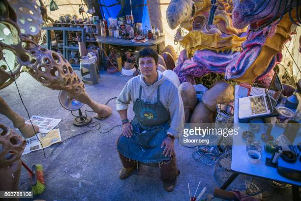 Artist Ricardo Linares sits for a photograph next to alebrijes Mexican folk art sculptures at his studio in Mexico City Mexico on Wednesday Oct 18...