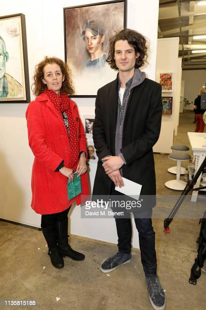 Artist Ru Knox and family member pose with his portrait from the Unmissable25 exhibition during the private view of The Other Art Fair at The Old...