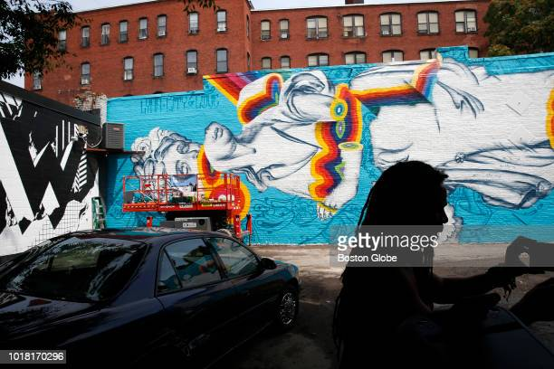 Artist Ruben Ubiera is silhouetted against the wall he painted for the second annual Beyond Walls Mural Festival in Lynn MA on Aug 14 2018