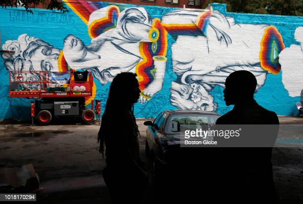 Artist Ruben Ubiera left is silhouetted against the wall he painted for the second annual Beyond Walls Mural Festival as he chats with a passerby in...