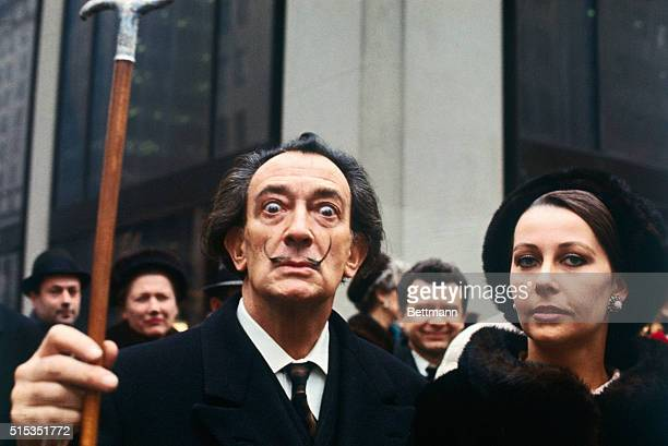 Artist Salvador Dali, lifting his cane, with a woman in New York.