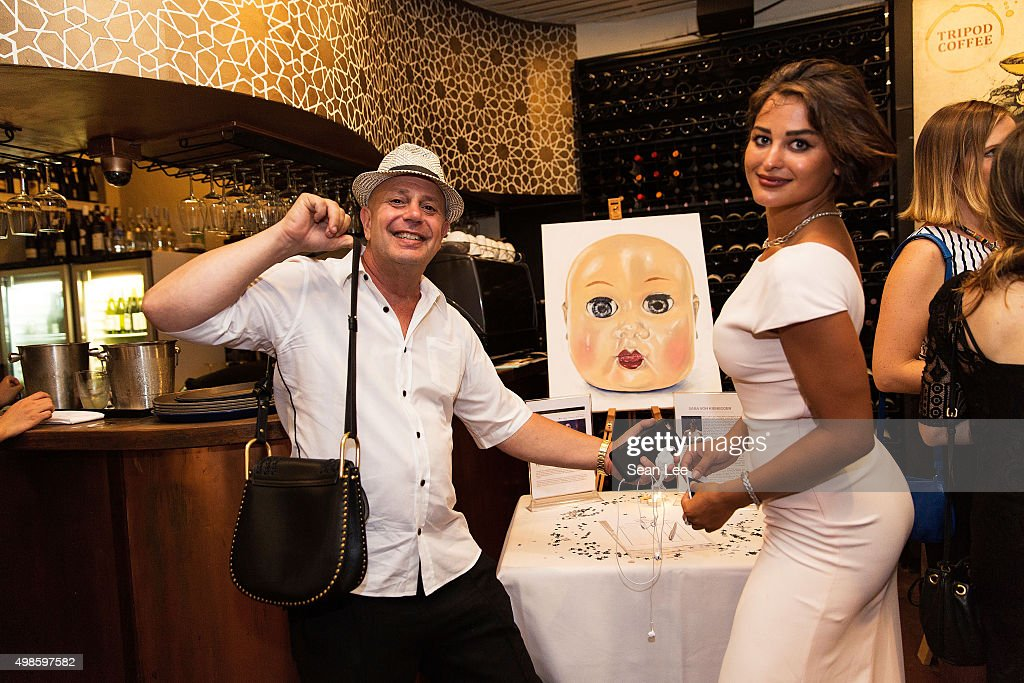 Artist Sara Von Kienegger (L) and party rocker Edward Bass stand in front of a painting by Sara Von Kienegger at the Original Sin hosted charity fund raising party for the benefit of Truyen Tin Orphanage on November 21, 2015 in Singapore.