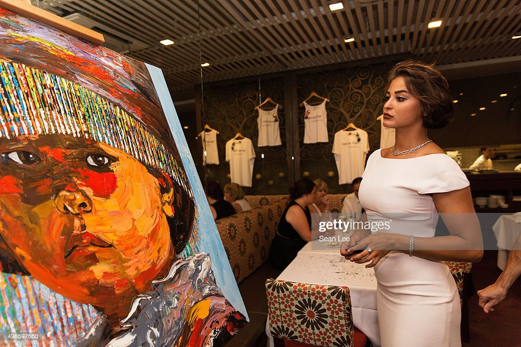 Artist Sara Von Kienegger looks at donated artwork at the Original Sin hosted charity fund raising party for the benefit of Truyen Tin Orphanage on November 21, 2015 in Singapore.