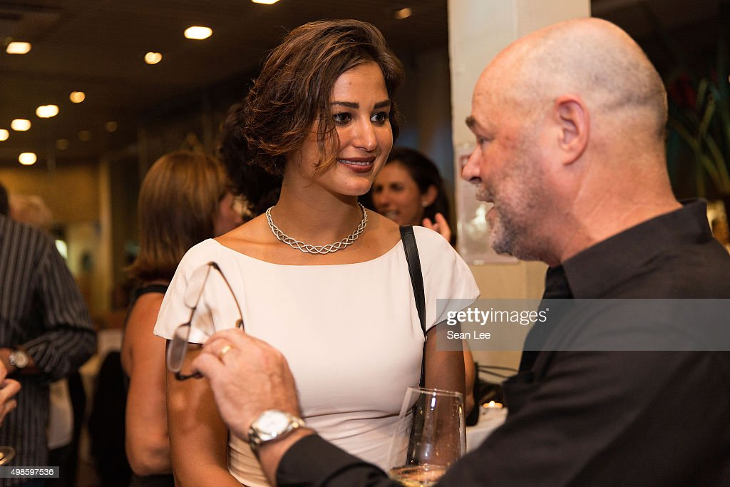 Artist Sara Von Kienegger (L) speaks to Bill Cornwell at the Original Sin hosted charity fund raising party for the benefit of Truyen Tin Orphanage on November 21, 2015 in Singapore.
